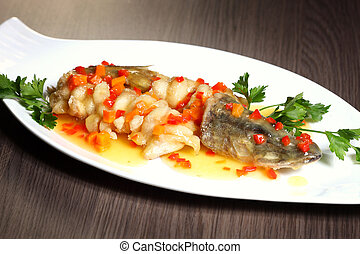 Grilled fish on white plate with herbs and lemon on wooden background, top view. Mediterranean luxurious seafood concept.