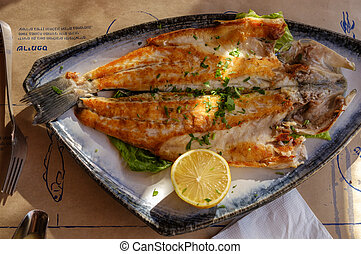 Grilled fish with lemon on a plate.