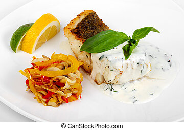 Grilled fish with sauce, vegetable salad and lemon