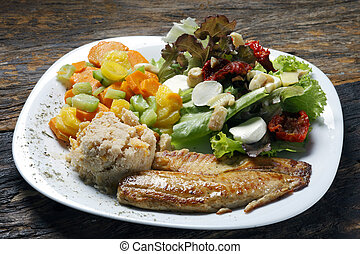 Grilled fish with vegetables and salad