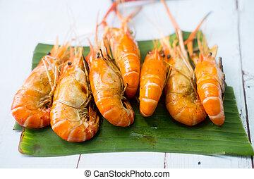 Grilled fresh shrimps on banana leaf background