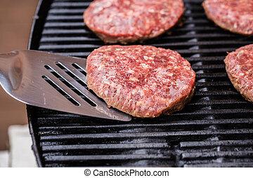 Grilled ground beef pattie burger on spatula against BBQ -...