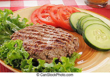 Grilled ground beef patty with vegetables - A juicy grilled...