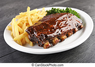Grilled juicy barbecue pork ribs in a white plate with fries...