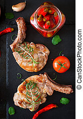 Grilled juicy steak on the bone with vegetables on a dark background. Top view