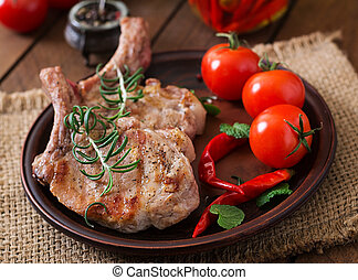 Grilled juicy steak on the bone with vegetables on a wooden background.