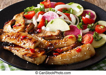 grilled king oyster mushrooms with sesame seeds and fresh vegetable salad close-up. horizontal