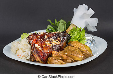 Grilled knuckle of pork, vegetables and potate on white plate