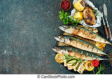 Grilled mackerel fish with baked potatoes on stone...