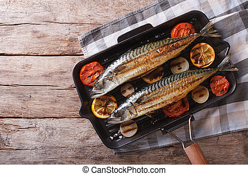 Grilled mackerel in pan with vegetables. horizontal top view...