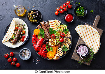 Grilled meat kebabs, vegetables on a black plate with tortillas, flat bread. Slate stone background. Top view.