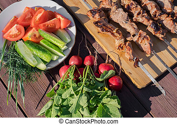 Grilled meat on skewers on a wooden background