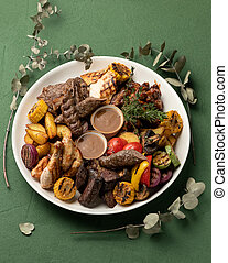 Grilled meat platter with vegetables isolated on green background. Barbecue concept. Vertical format, top view