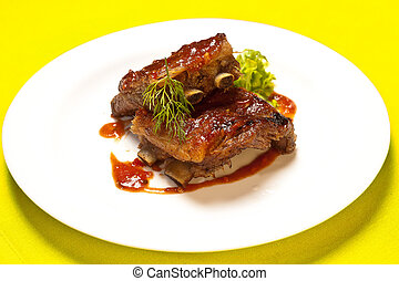 Grilled meat ribs on white plate