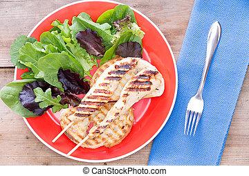 Grilled meat served with leaf vegetables