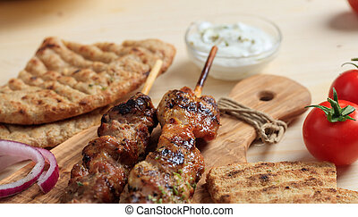 Grilled meat skewers on a wooden surface