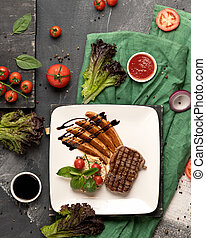 Grilled meat steak and potatoes cooking. White square food plate on kitchen table covered with green square. Blank for restaurant advertising banner. High angle view. Vertical format 4x5