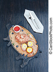 Grilled meat with corn and sauce on a cutting wooden board. wooden background. top view