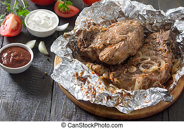 Grilled meat with sauce and vegetables on a dark rustic background, top view, frame. Food Concept Thanksgiving.