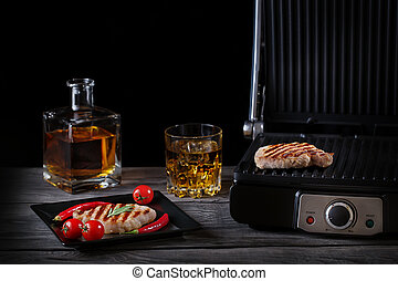 Grilled meat with vegetables and whiskey on wooden table