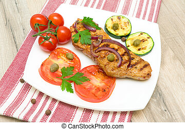 Grilled meat with vegetables on a plate. horizontal photo.