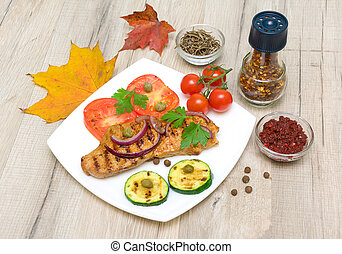 Grilled meat with vegetables on a plate, spices and autumn leaves. horizontal photo.