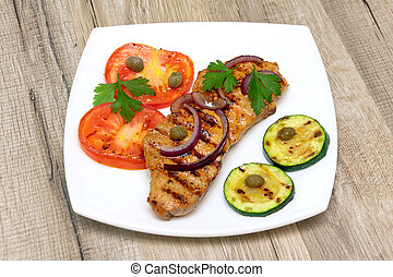 grilled meat with vegetables on a wooden background
