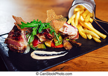 Grilled meat with vegetables on black stone table.