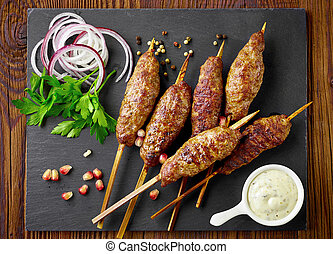 grilled minced meat skewers kebabs on black stone cutting ...