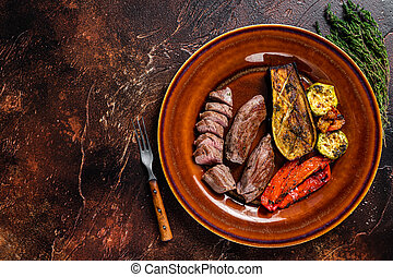 Grilled mutton tenderloin Fillet Meat, lamb sirloin on rustic plate with vegetables. Dark background. Top view. Copy space