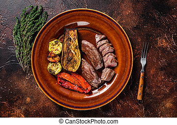 Grilled mutton tenderloin Fillet Meat, lamb sirloin on rustic plate with vegetables. Dark background. Top view