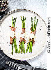 Grilled organic asparagus wrapped in pork bacon. Gray background. Top view