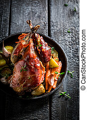 Grilled pheasant with bacon and vegetables on dark...