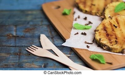 Grilled pineapple slices on wooden table.