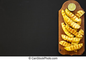 Grilled pineapple wedges on a rustic wooden board on a black background. Summer food. Copy space.