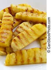 Grilled pineapple wedges on a white plate, closeup. Summer food. Side view.