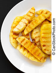 Grilled pineapple wedges on a white plate on a black background. Summer food. Close-up.