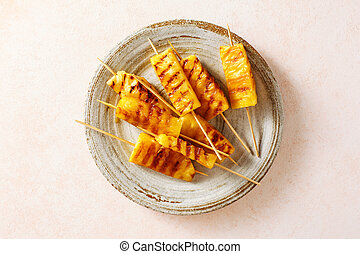Grilled pineapple wedges on wooden skewers on a plate Close ...