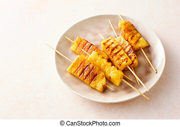 Grilled pineapple wedges on wooden skewers on a plate