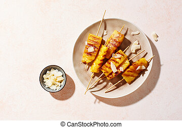 Grilled pineapple wedges on wooden skewers on a plate, top ...