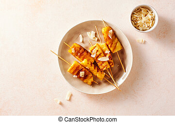 Grilled pineapple wedges on wooden skewers on a plate. Top ...
