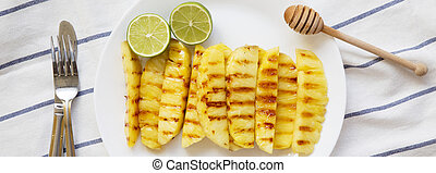 Grilled pineapple wedges with lime on white plate, overhead view. Summer food. From above, flat lay.