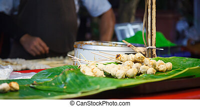 Grilled Pork and Beef Meat Ball Sticks and dipping sauce pot placed on green banana leaf shelf in street food market stall. Traditional fast food menu served at casual local eateries in Thailand, Asia