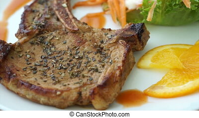 Video of grilled pork chop steak with bone. Colorful salad and orange sauce