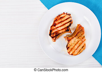 grilled pork chops on a white dish. top view