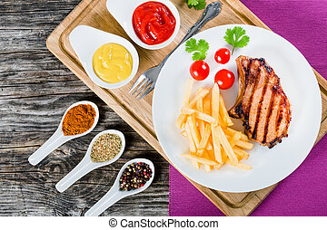 grilled pork chops on a white dish, top view