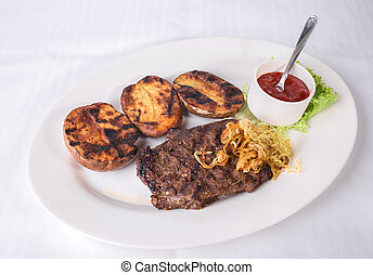 Grilled pork cutlet with roasted potatoes.