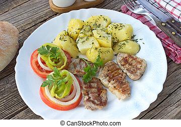 Grilled pork fillet meat and vegetables on plate