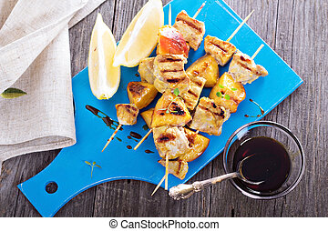 Grilled pork kabobs with peaches served on a cutting board