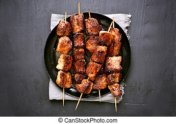 Grilled pork kebabs on dark background, top view